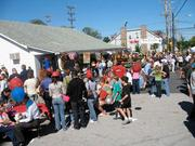 A crowd gathers to celebrate Highland Day around local business Boarman's.