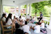 An upper school class outdoors on the porch, at Bryn Mawr School.