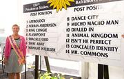 The Ms. Preakness Pink Warrior 2011 Susan Faber stands alongside the board displaying the post position draws for the Preakness.