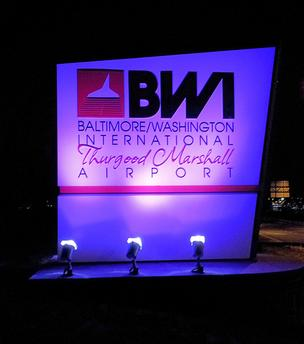 A sign outside Baltimore/Washington International Thurgood Marshall Airport glows purple.