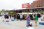 Race fans play an improvised game of cornhole Friday prior to the start of the Baltimore Grand Prix's practice session.