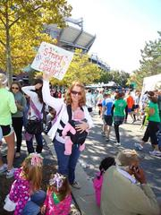 A wife, along with her kids, hold a sign supporting her husband, a participant in the 13.1-mile half marathon.