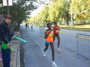 A full-marathon runner passes a spectator along mile 16 on Linwood Avenue across from Patterson Park.