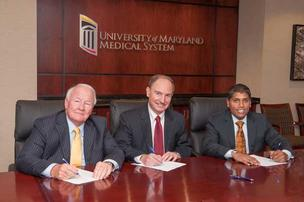 Francis X. Kelly, chairman of the University of Maryland St. Joseph Medical Center; Robert A. Chrencik, CEO of UMMS; and Dr. Mohan Suntha, CEO of the University of Maryland St. Joseph Medical Center, signing an agreement Friday at the closing of the acqu