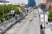 Cars from the Izod IndyCar Series race down Pratt Street Friday morning during a practice round.