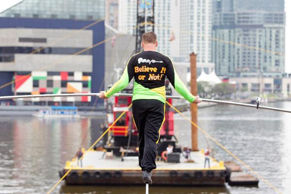 Nik Wallenda, a world renowned tightrope walker, crosses Baltimore's Inner Harbor on Wednesday as part of a stunt for the opening of Ripley's Believe It or Not! He was more than 90 feet in the air.