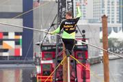 Nik Wallenda, a world renowned tightrope walker, takes a knee and waves to the crowd halfway through his journey across the Inner Harbor. He was more than 90 feet in the air.