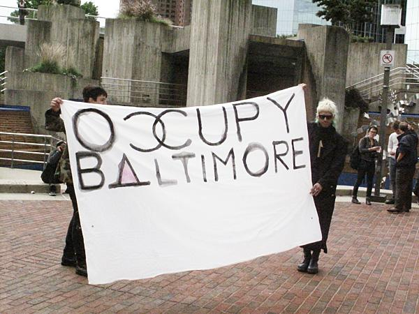 Two protestors stand at the Inner Harbor on Tuesday as part of Occupy Baltimore.