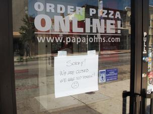 A sign on the door Monday of a Papa John's along Eastern Avenue in Highlandtown notifies customers the store is closed due to no power.