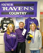 McDaniel College Office of Human Resources is Ravens-themed for Purple Friday. From left, Kristin Massicot, benefits and employment manager;  Thomas Steback, human resources director; Dawn Gold, departmental secretary.