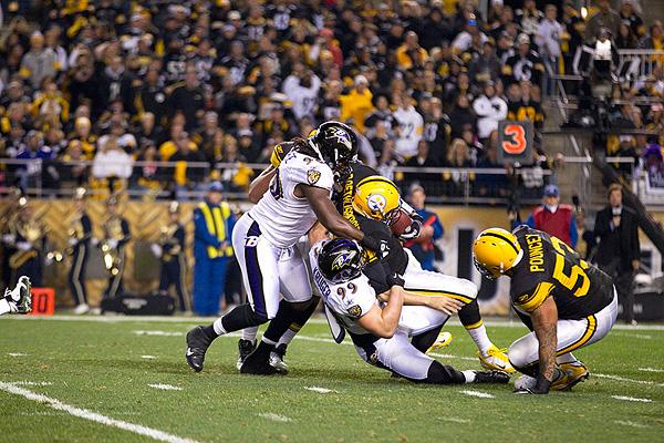 Ravens linebacker Paul Kruger, No. 99, wraps up and sacks Steelers quarterback Ben Roethlisberger. The Ravens defeated the Steelers 23-20.