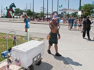 Joshua Anderson, who selling water and miniature American flags along Pratt Street on Friday, shouts on a megaphone in an attempt to draw customers.