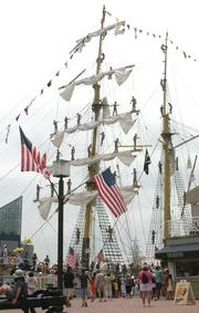 Spectators gather at the Inner Harbor to watch the tall ships depart on Tuesday.