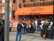 People waited in line Monday morning to get inside Sliders Bar and Grille along Russell Street.