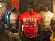 Johns Hopkins, University of Maryland and Navy shirts on display at Under Armour's new store.