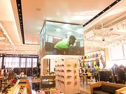 A seven-foot tall LED board with 330,000 lightshangs above the footwear section of Under Armour's new Brand House in Baltimore.