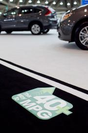 Stickers placed on the Convention Center floor direct consumers to vehicles boasting 40 miles per gallon or more.