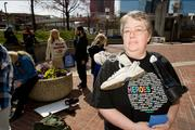 """Beth Emmerling led a protest on Thursday of a Bank of America branch in Baltimore. She held a sign during the march that red """"Walk a mile in our shoes & stop foreclosures."""""""