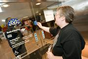 Beth Emmerling knocks of the door of a Bank of America branch in downtown Baltimore. The bank was closed as protestors arrived.