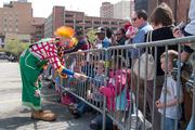 A circus clown entertains children Wednesday afternoon outside Lexington Market.