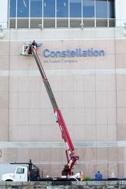 Workers on Thursday place a new Constellation sign on the side of the company's 750 E. Pratt St. office tower downtown. Constellation was acquired earlier this year by Exelon Corp.