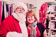Santa helps bring in holiday cheer at Susanna Siger's Hampden store, Ma Petite Shoe. Siger, on right, says she didn't count on a dramatic sales increase this year.