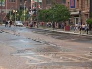 Water flows down Light Street during Monday's rush hour following a large water main break.