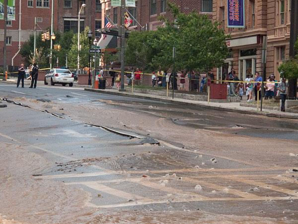 Water runs down Light Street on Monday night after a 20-inch water main erupted.