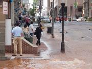 Water streams down Light Street during Monday's rush hour following a large water main break.