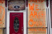 A partially boarded up One Eyed Mike's in Fells Point lets patrons know the  pirate-themed bar is still open for business on Monday despite Hurricane  Sandy.