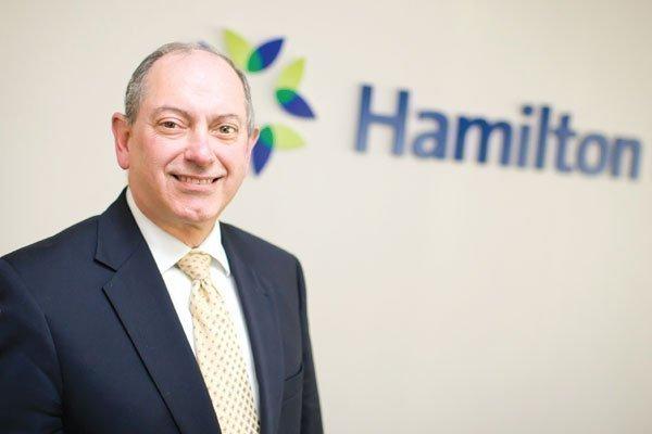Hamilton Bank CEO Robert DeAlmeida shows off the bank's new signs.