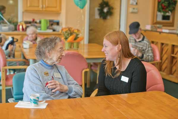 Carrie Grafton, right, center director of Winter Growth, chats with resident Nellie Perugini. Grafton worries that a proposed license fee hike will force her facility to pass additional costs on to residents.