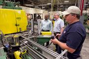 Engineering manager G. Bryan Powell, in front, works the production line. CEO Rick Huether, center, and machinist Thomas Cardwell look on.