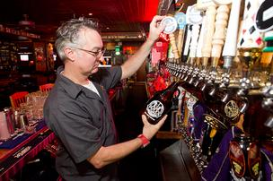 Manager Robert Simko tops off a growler at Max's Taphouse.