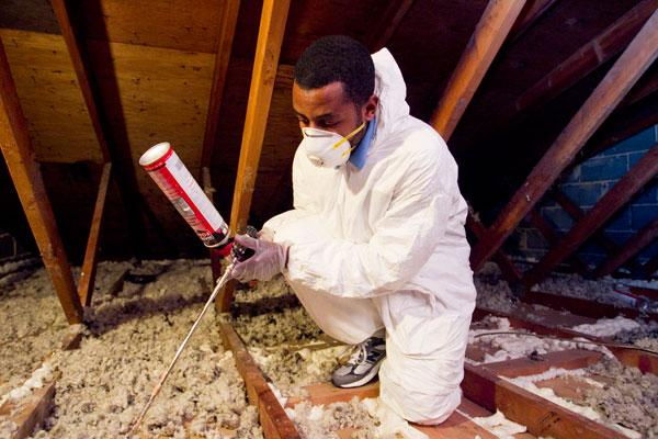 Dontae Burgess of the Baltimore Center for Green Careers uses insulation to cut energy loss in a Southwest Baltimore home.