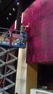 A worker puts the finishing touches on the Everyman Theatre's lobby. The building has been under construction for about two years.