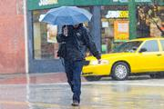 A pedestrian braces the rain on Monday in Fells Point. As much as 8 inches of rain is expected in Baltimore during Hurricane Sandy.