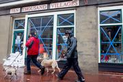 Two men walk with dogs along a rain-soaked Broadway in Fells Point on Monday.