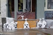 With Halloween just days, a building in Fells Point is lined with sandbags painted with ghost faces.
