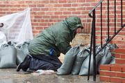A man spreads sand bags in front of a home in Fells Point as Hurricane Sandy hunkers down on Baltimore.
