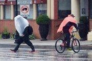 Commuters along President Street downtown on Monday brace the rain from Hurricane Sandy.