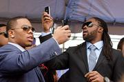 Ray Rice, left, and Torrey Smith capture images at the Ravens sendoff rally on Monday. The team will play in Super Bowl XLVII on Feb. 3 in New Orleans.