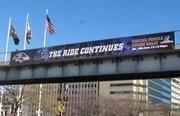 A sign on a pedestrian bridge above Pratt Street honors the Ravens' playoff run.