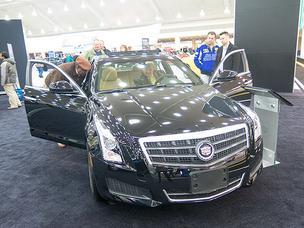 Above, visitors to the 2013 Baltimore Auto Show view a Cadillac ATS. A new report says the average Baltimore household can afford to spend $24,042 on a new car.