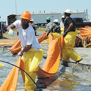 Workers clean up the Alabama Gulf Coast following the April 2010 oil spill. BP has reached a $7.8 billion settlement with thousands of plaintiffs seeking damages from the spill.