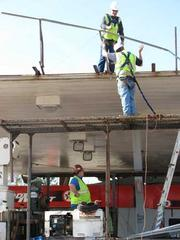 Workers tend to the roof of a Texaco station that was damaged in Monday's storm.