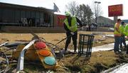 Dwayne Gillam, Alabama Department of Transportation employee, shovels rubble in front of the badly damaged Wells Fargo bank branch on Center Point Parkway.
