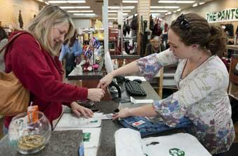 Susan Rochester, left, signs her credit card receipt with the help of Jennifer Grooms at the Pants Store in Trussville.