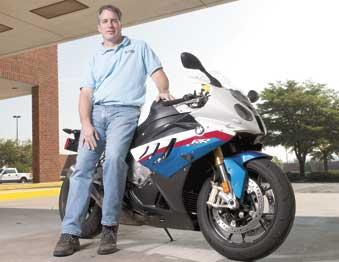 Jim Lewis leans on one of his bikes outside of his BMW Motorcycles of Birmingham dealership in Crestwood. He's hoping to relocate the dealership to Leeds by April 2014.
