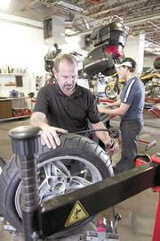 Glenn West, left, inflates a tire while Andy Carroll, right, works in the service area of BMW Motorcycles of Birmingham's new location in the former Sears Auto Center at Century Plaza.